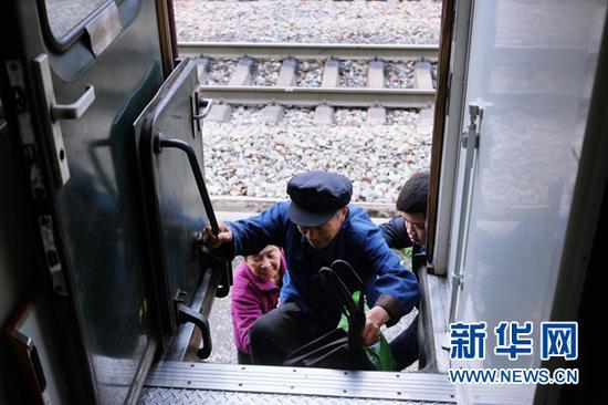 两位老人在列车员帮助下登上6905/8列车。(4月24日摄)新华网陈俊松 摄