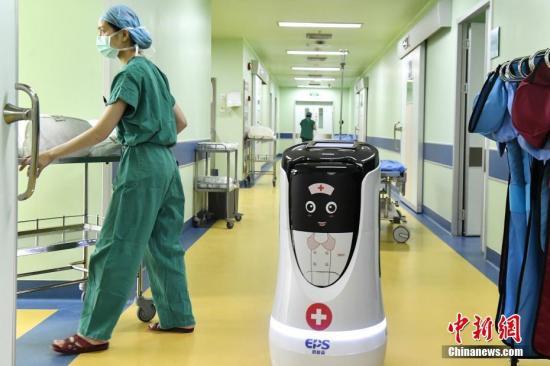 4月3日,AI(人工智能)医生助手为医生运送手术所需工具。中新社记者 陈骥�F 摄