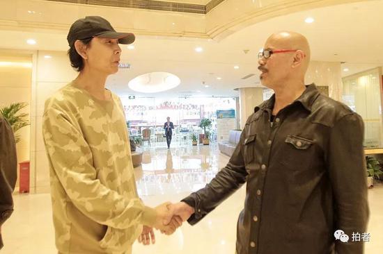 ▲阮小七饰演者李冬果和阮小五饰演者张衡平握手。