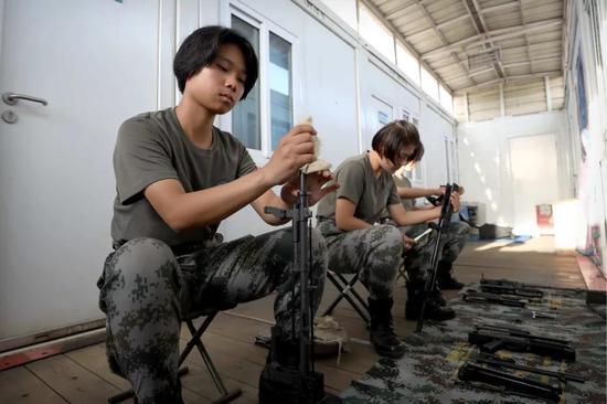 4月30日,于培杰在女兵宿舍和战友擦拭枪支。