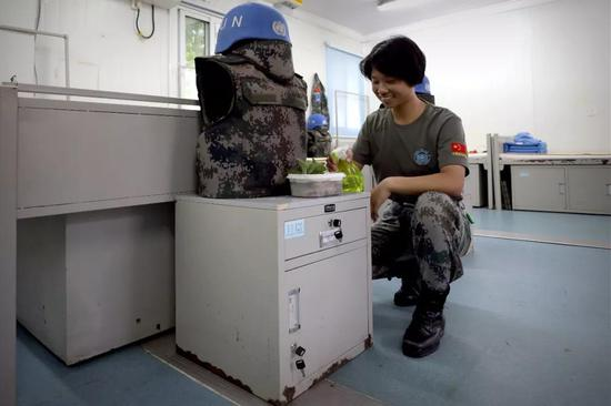 4月30日,于培杰在女兵宿舍给植物浇水。