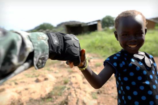 4月30日,于培杰在朱巴市皇后村巡逻时与一名儿童握手。