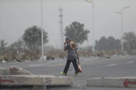 ↑北京今日大风中带有沙尘,东五环外,董村附近一处在建工地旁,大量裸露未覆盖的土堆,让这沙尘天更加昏暗了。 甘南摄
