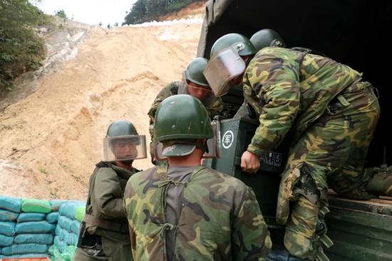 官兵将地雷和爆炸物从车上搬下来
