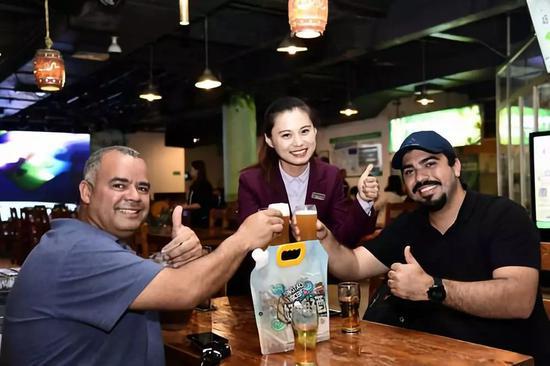 2018年5月17日拍摄的在青岛啤酒博物馆,外国游客举起青岛啤酒干杯。新华社记者郭绪雷摄