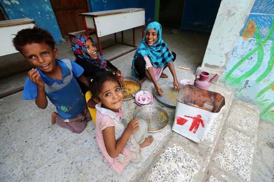 6月18日,从也门荷台达机场附近村庄撤离的儿童在荷台达一所作为临时安置点的学校里吃饭。新华社/路透