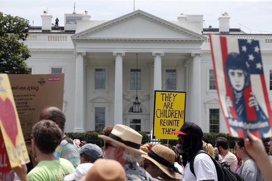 图为抗议民众经过白宫。(美联社)