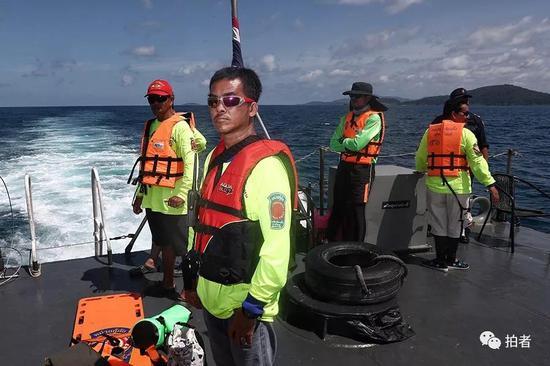 △ 泰国的救援人员在救援军舰的甲板上待命。