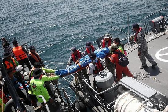△军舰上的一部分遇难者遗体由其他船只运往码头。