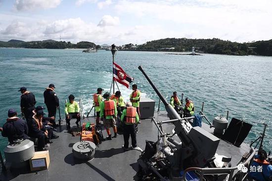 △ 泰国的救援人员在军舰的甲板上待命准备。