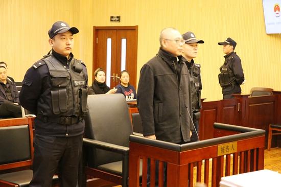 △2017年12月22日,李晓明在长春市中院受审。图片来源/长春市检察院官网