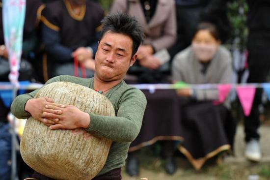 2018年3月30日,西藏林芝市巴宜区真巴村的村民在进行抱石头比赛。新华社记者张汝锋摄
