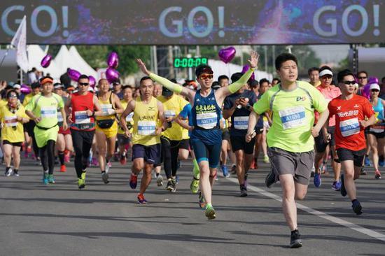 2018年5月13日,2018北京通州半程马拉松和2018中国(北京·通州)残疾人半程马拉松开跑,共有8000多名跑步爱好者参加,其中300余名选手参加了残疾人半程马拉松的比赛。新华社记者鞠焕宗摄