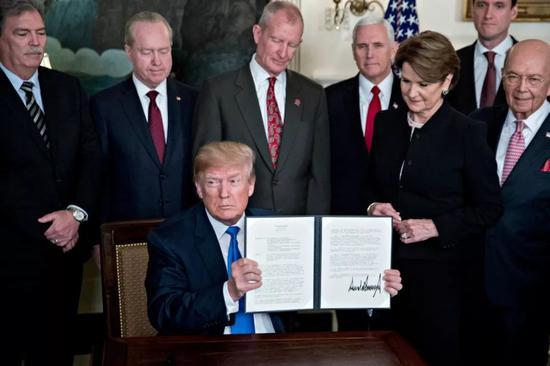 ▲资料图片:2018年3月22日,特朗普签署针对中国的备忘录。(彭博新闻社)