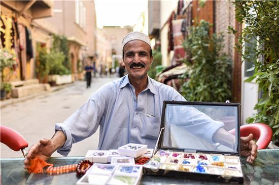 在喀什老城,来自巴基斯坦的商人在展现本人的各种珠宝(7月10日摄)。新华社记者赵戈摄