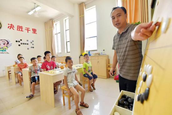 △2018年,江西省一青少年校外活动中心学生正在听老师讲解围棋技法。