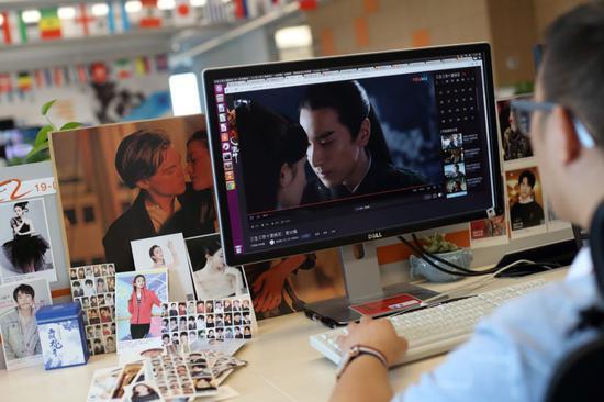 """▲2018年8月3日,北京,油库公司,29岁的吉恒杉是一名人工智能标注员,他正在训练机器识别何为""""接吻""""镜头,因此也被戏称为""""吻戏鉴定师""""。图片:VCG"""