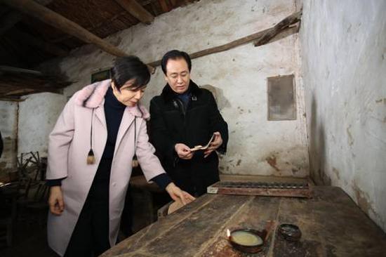 """許家印和妻子丁玉梅在堂屋看着老物件回憶:""""小時候條件很苦,每天晚上都是點着煤油燈,趴在這個小方桌上寫作業。"""""""