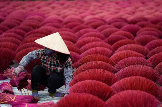 ▲1月3日,一名制香工人在越南河内附近的一座村庄工作。(新华社/法新社)