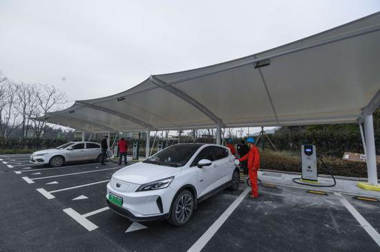 1月19日,在浙江德清县下渚湖景区内,工作人员在新投运的电动汽车快充站为游客的电动车充电。