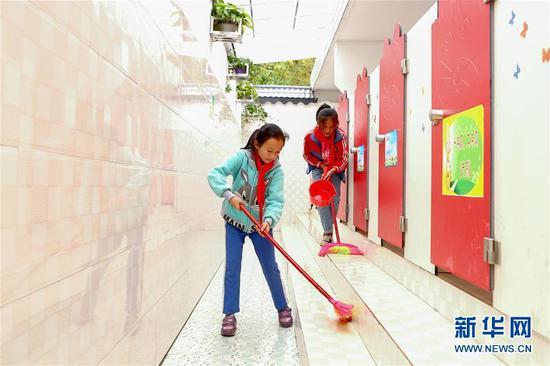 两名学生在贵州省织金县熊家场镇小学的厕所打扫卫生(2018年10月23日摄)。新华社记者 张玉薇 摄