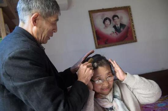 4月11日,老伴陈洪明为准备给视障人士解说电影《可可西里》的吴素环梳头。