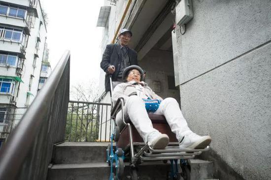 4月11日,在桐庐县桐君街道,老伴陈洪明推着吴素环下楼前往中国盲文图书馆桐庐县支馆为视障人士解说电影。