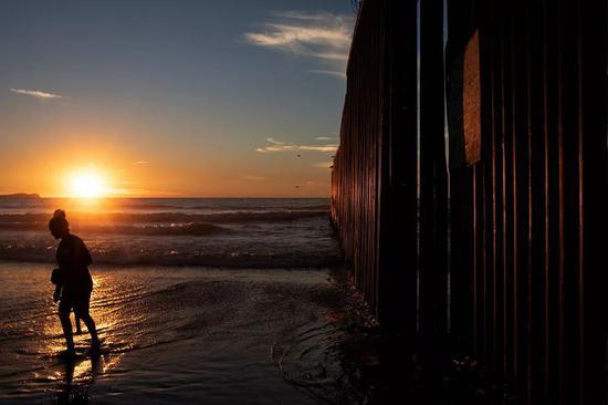 當地時間2018年12月3日,滯留美墨邊境地帶的中美洲移民企圖偷偷越過邊境線進入美國。/視覺中國