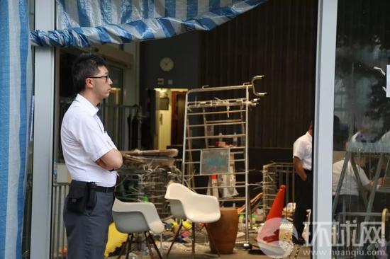 一位香港立法会的工作人员站在立法会入口处一侧,另一侧的门已经残破不堪。