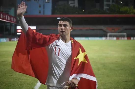 ▲9月10日,中国队球员艾克森身披国旗庆贺角逐成功。(新华社)