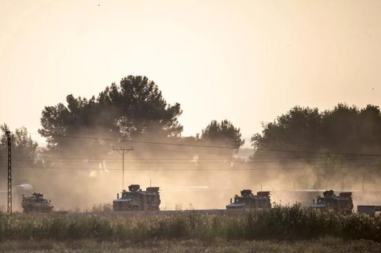 10月9日,在土耳其桑利乌尔法省阿克恰卡莱附近,土耳其军用车辆驶向叙利亚边境。新华社/法新
