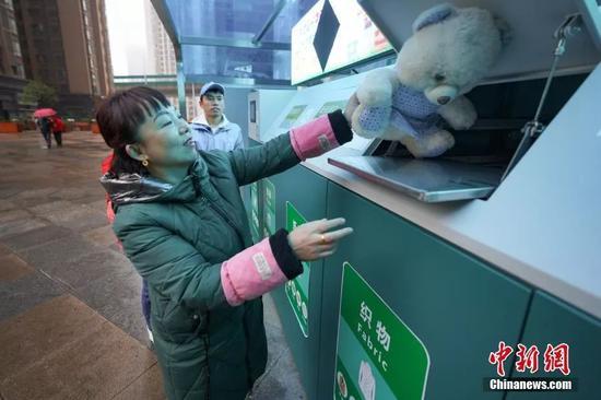 """11月26日,在贵阳市花果园社区,市民将布偶熊投放到垃圾分类智能回收机的""""织物""""类回收箱。中新社记者 贺俊怡 摄"""