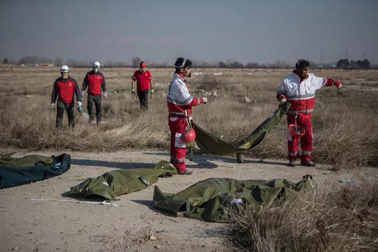 1月8日,在伊朗德黑兰霍梅尼国际机场附近,救援人员在坠机现场工作。新华社发(艾哈迈德·哈拉比萨斯摄)