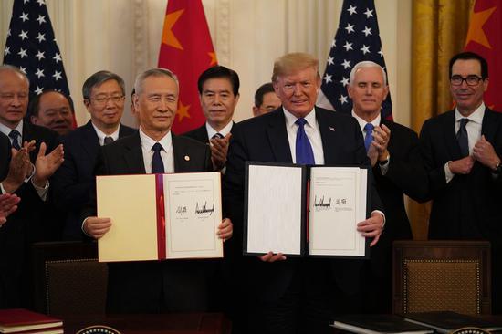 ↑ 1月15日,刘鹤与特朗普在华盛顿白宫东厅展示协议文本。新华社记者 王迎 摄