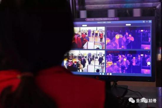 ▲ 1月21日,武汉火车站,工作人员通过仪器对旅客体温进行检测。摄影/新京报记者 游天燚