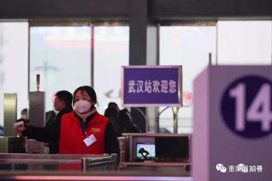 ▲1月21日,武汉火车站,工作人员拿着体温检测仪检测经过进站闸机的体温。摄影/新京报记者 游天燚
