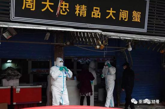 ▲1月21日16时许,武汉华南海鲜批发市场西侧五十米,防疫工作人员对一生鲜商户进行检查。摄影/新京报记者 游天燚