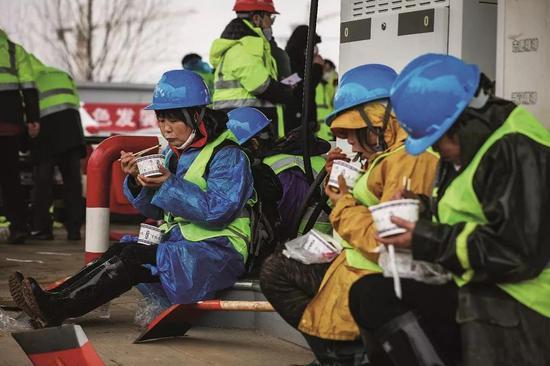 2020年1月24日,夏历除夕,在武汉火神山医院施工现场吃年饭的工人。摄影/陈卓