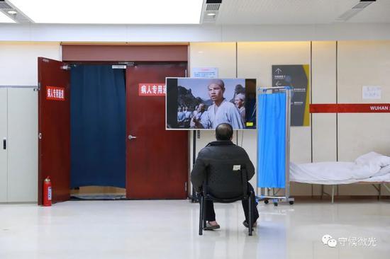 2月21日,武汉市洪山体育馆方舱医院A区内,一名患者在看电视。中青报·中青网见习记者 鲁冲/摄