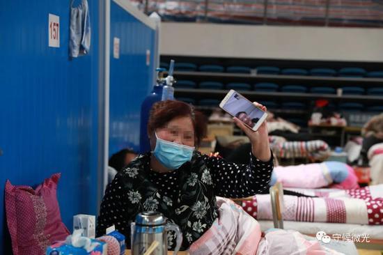 2月21日,武汉市洪山体育馆方舱医院A区内,一名患者正在与家族视频通话,给家族看方舱医院里面的环境。中青报·中青网见习记者 鲁冲/摄