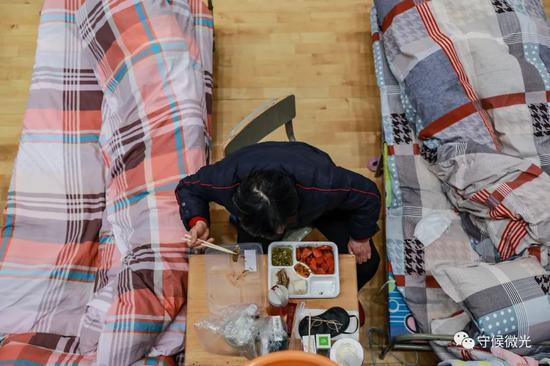 2月21日,武汉市洪山体育馆方舱医院A区内,一名患者在吃晚饭。中青报·中青网见习记者 鲁冲/摄