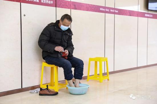 2月21日,武汉市洪山体育馆方舱医院A区内,一名患者在泡脚,他筹办换上新的袜子。中青报·中青网见习记者 鲁冲/摄