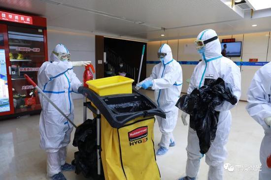 2月21日,武汉市洪山体育馆方舱医院A区内,保洁人员正在对垃圾进行消毒处置。中青报·中青网见习记者 鲁冲/摄