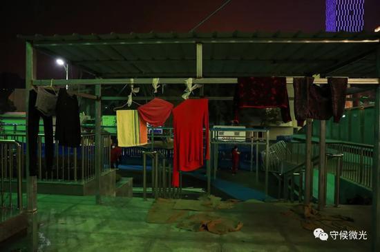 """2月21日,武汉市洪山体育馆方舱医院A区外,""""晾衣杆""""上挂满了衣服。中青报·中青网见习记者 鲁冲/摄"""