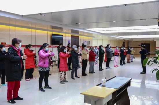 """2月21日,武汉市洪山体育馆方舱医院A区内,""""组长""""张明(假名,右一)正在领导患者做健肺操。A区内会细分出各个区域,每区域选一位患者当组长,卖力协助医护人员统计、拿饭、上报环境等等。中青报·中青网见习记者 鲁冲/摄"""