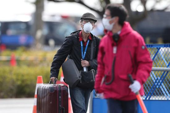 """2月19日,在日本横滨,一名""""钻石公主""""号邮轮乘客(左)下船后离开港口。"""
