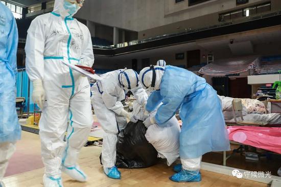 2月21日,武汉市洪山体育馆方舱医院A区内,医护人员在收拾出院病人的床上用品。接下来,他们会换一整套全新的床上用品。中青报·中青网见习记者 鲁冲/摄