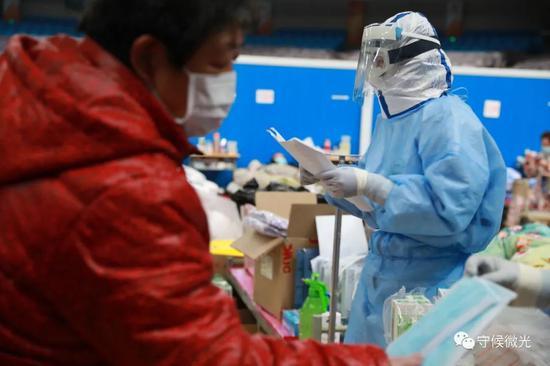2月21日,武汉市洪山体育馆方舱医院A区内,患者在医护人员处领取口罩。中青报·中青网见习记者 鲁冲/摄