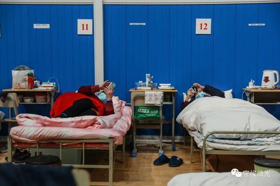 2月21日,武汉市洪山体育馆方舱医院A区内,两名患者躺在床上看手机。中青报·中青网见习记者 鲁冲/摄