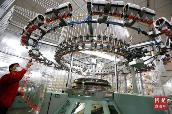 2月22日,在位于山东青岛市即墨区的青岛即发集团有限公司生产车间里,工人在染整生产线上忙碌。中新社发 梁孝鹏 摄
